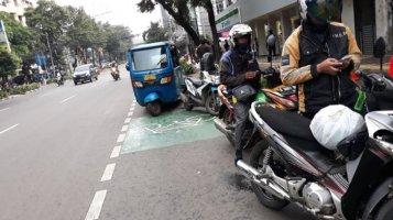 Jalan Melawai, Jakarta. Usaha untuk menghadirkan jalur bersepeda secara khusus di Jakarta, salah satunya bisa diapresiasi di sepanjang jalan Melawai. Namun sayangnya, inipun secara teknis masih setengah-setengah. Secara literal, setengah terpisah dan setengah tidak (hanya sharrow), juga kurang tersinergi dengan berbagai fitur jalan, dan juga dukungan regulasi. Menghasilkan pemandangan klasik, digunakan sebagai lahan parkir, termasuk kendaraan publik dan ojek online. Dokumentasi tahun 2018. Sumber: http://jakarta.tribunnews.com/2018/02/09/duh-driver-online-tunggu-order-di-jalur-sepeda
